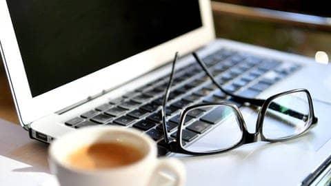 Brille auf Lapop und Kaffeetasse (Foto: dpa / picture-alliance)