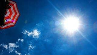 Sonne brennt, Sonnenschirm und blauer Himmel (Foto: dpa Bildfunk, dpa-Zentralbild)