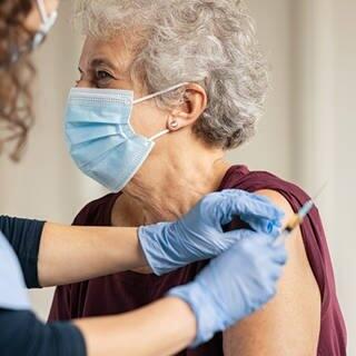 Ältere Frau mit medizinischem Personal bei der Impfung (Foto: Adobe Stock / Rido)