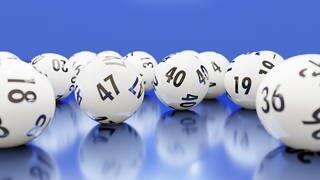Verschiedene Bälle aus der Lotterie auf einem blauen Untergrund  (Foto: Adobe Stock / Fiedels)