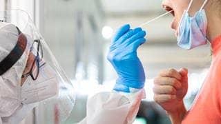 Ein Mitarbeiter der Johanniter-Unfall-Hilfe nimmt für einen Cotrona-Test einen Abstrich von einer Frau.  (Foto: dpa Bildfunk, Picture Alliance)