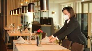 Eine Gastwirtin mit Mundschutz richtet einen Tisch in einem leeren Restaurant ein. (Foto: dpa Bildfunk, picture alliance/dpa/dpa-Zentralbild | Matthias Bein)