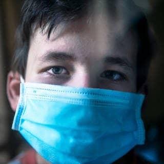 Ein trauriger Junge trägt eine Maske (Foto: Imago, Imago)