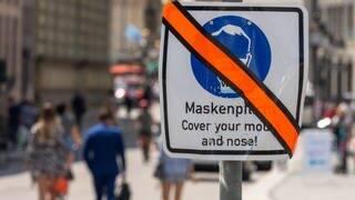 Ein mit orangen Klebeband durchgestrichenes Schild mit der Aufschrift «Maskenpflicht - Cover your mouth and nose!» steht in der Innenstadt am Straßenrand. (Foto: dpa Bildfunk, picture alliance/dpa   Peter Kneffel)