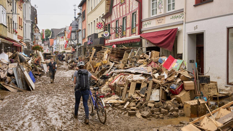 Ahrweiler: Eine Frau schiebt ihr Fahrrad durch den Schlamm.