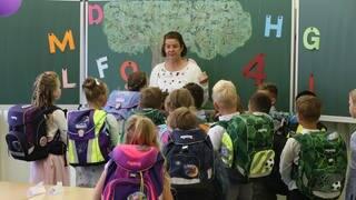 Schülerinnen und Schüler stehen mit ihren Schulränzen vor einer Lehrerin im Klassenraum. (Foto: dpa Bildfunk, picture alliance/dpa/dpa-Zentralbild   Matthias Bein)
