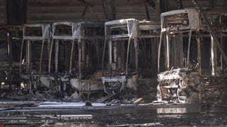 Ausgebrannte Omnibusse stehen in einem Busdepot. Nach einem Großbrand in dem Depot ist die Ursache des Feuers weiterhin unklar. (Foto: dpa Bildfunk, picture alliance/dpa | Marijan Murat)