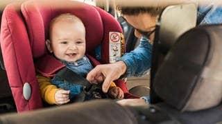 Baby wird im Kindersitz angeschnallt (Foto: AdobeStock / Trendsetter Images)