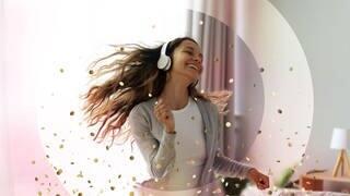 Frau mit Kopfhörern tanzt durchs Wohnzimmer (Foto: Adobe Stock/fizkes)